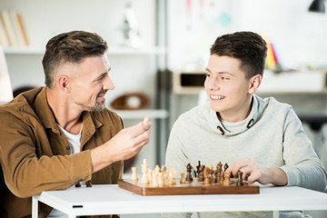 smiling father and teen son playing chess at home and looking at each other