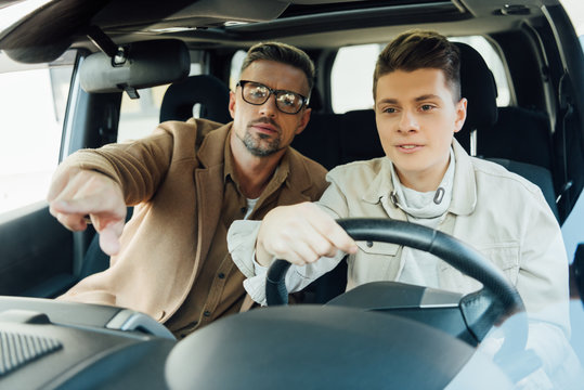 handsome father pointing on something while teaching teen son driving car