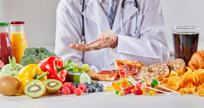 Doctor in coat comparing good and bad food