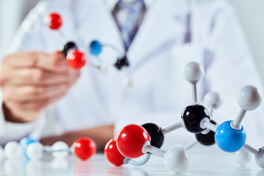 Scientist with coloured molecular structure models