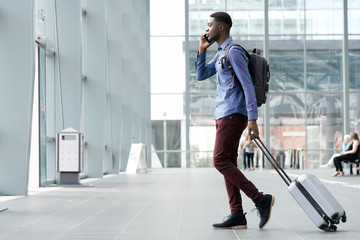 side portrait of young african man traveling with suitcase and cellphone at airport Wall mural