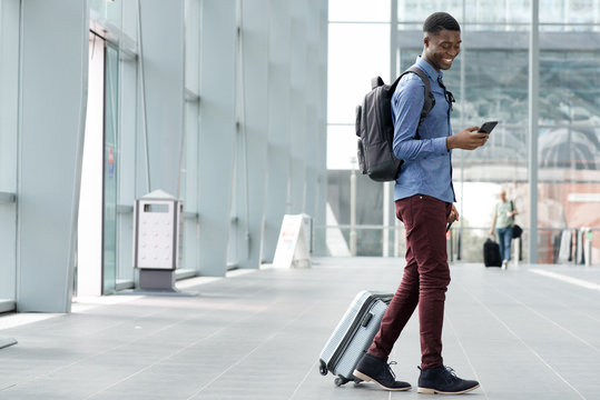 Full body side of young black man traveling with suitcase and cellphone at airport