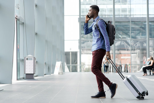 side portrait of young african man traveling with suitcase and cellphone at airport