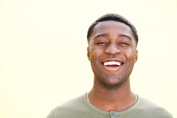 horizontal portrait of laughing african american man against green background