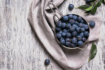 Blue blackthorn berries in metallic bowl on a table