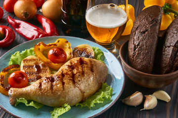 Grilled chicken leg with vegetables and light beer on a blue plate