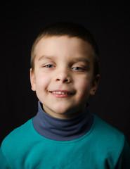 boy on a dark background smiling