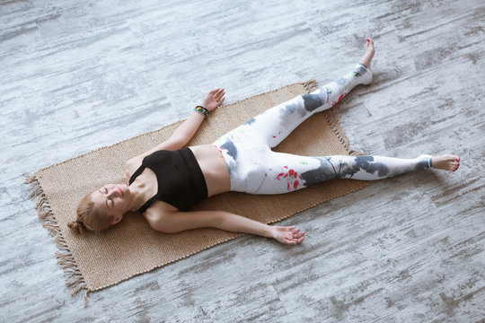 Adult woman meditating in savasana pose on bamboo yoga mat after working out at home and doing yoga exercise. Shavasana Posture, meditation, resting after practice, breathing.