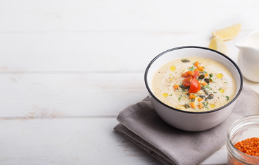 Lentil soup puree with tomatoes, cucumber and nuts in a bowl on a white wooden background