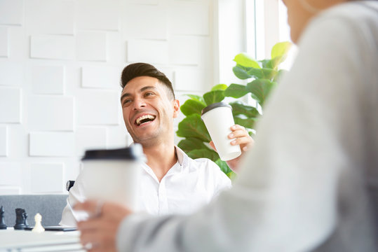 A man in casual white shirt is laughing and drinking coffee while having a meeting with his colleagues in the greenery white office pantry.