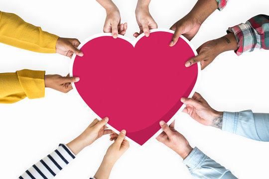 Diverse hands holding a red heart