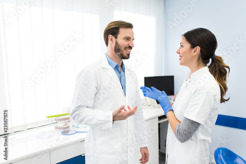 Beautiful young dentists talking and smiling, working