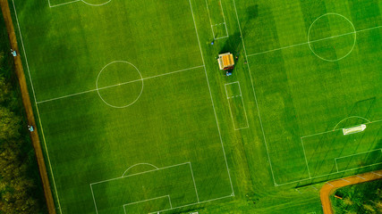 Aerial image over artificial grass football pitches. Long shadows thrown by a low sun.