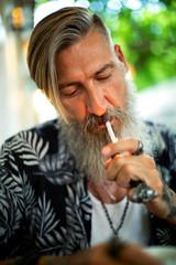 Porträt eines bärtigen Mannes in Coffee shop mit Zigarette im Mund.
