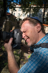 Closeup portrait of a male tourist photographer with a jewish hat holding a camera taking a shot.