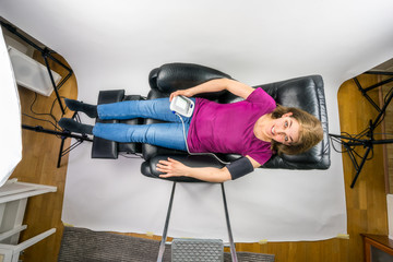 Above view of mature woman lying down in recliner chair holding a blood pressure machine. Behind the scene photo session.