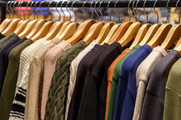 Multicolored woolen knitted sweaters hanging on hangers close-up, side view