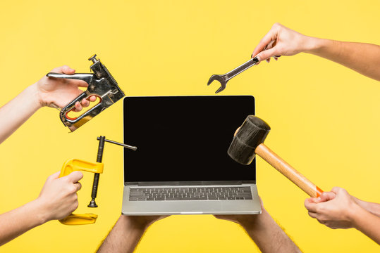 cropped shot of hands holding tools and laptop with blank screen isolated on yellow