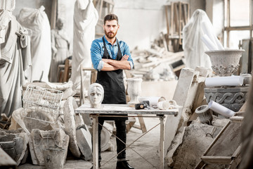 Portrait of a handsome sculptor in blue t-shirt and apron working with stone sculptures on the table at the old atmospheric studio