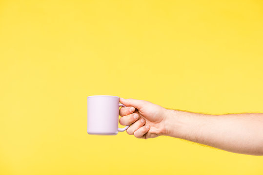cropped shot of person holding white cup isolated on yellow