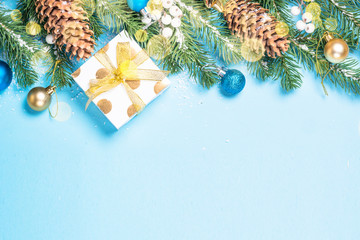 Snow Fir tree branch with blue and golden decorations and present box on blue background.