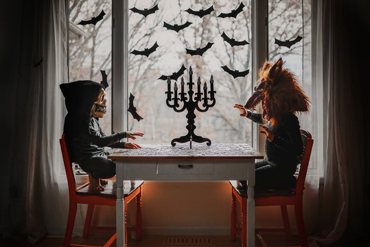 Two children in Halloween costumes sitting by a window doing a jigsaw puzzle, United States