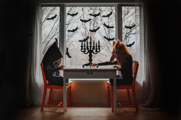 Two children in Halloween costumes sitting by a window doing a puzzle, United States
