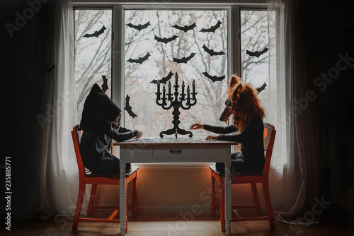 Children in Halloween costumes playing with puzzles by window