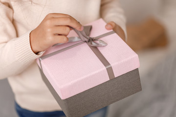 Child hands holding beautiful pink gift box