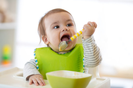 Happy cute infant baby boy spoon eats itself