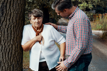 Helpful pedestrian taking care of senior woman having heart attack on the street