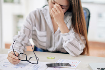 Young overworked woman holding eyeglasses and rubbing eyes while sitting at desk in office