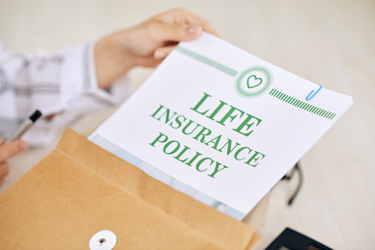Crop worker of agency holding paper document of life insurance policy in envelope