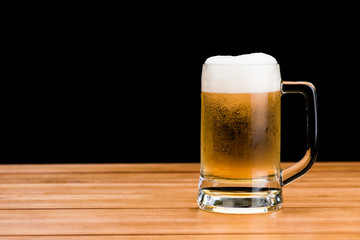 Glass of beer on wood table isolated on black background , drinking alcohol celebration object concept design