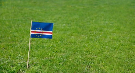 Cape Verde flag. Photo of Cape Verde flag on a green grass lawn background. Close up of national flag waving outdoors.