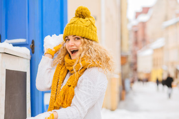 Curly blonde woman playing snowballs wearing white sweater yellow knitted funny hat with a bubo, scarf and gloves outdoor over city street perspective background in winter snowy day.
