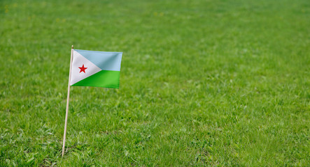 Djibouti flag. Photo of Djibouti flag on a green grass lawn background. Close up of national flag waving outdoors.