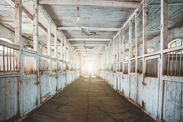 Inside old wooden stable or barn with horse boxes, tunnel or corridor view with light in the end