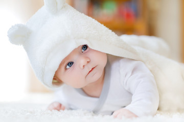 Baby girl with blue eyes wearing white towel or winter overal in white sunny bedroom. Newborn child relaxing in bed. Nursery for children. Textile and bedding for kids. New born kid with toy bear