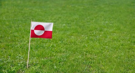 Greenland flag. Photo of Greenland flag on a green grass lawn background. Close up of national flag waving outdoors.