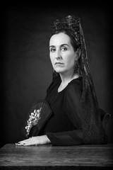 Spanish woman sitting at a wooden desk wearing the traditional black veil (mantilla) and high comb (peineta).