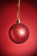 Christmas decoration with red Ball on red background with snowflakes falling from sky. Happy holidays composition.