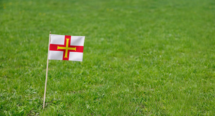 Guernsey flag. Photo of Guernsey flag on a green grass lawn background. Close up of national flag waving outdoors.