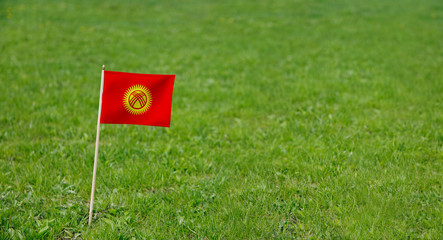Kyrgyzstan flag. Photo of Kyrgyzstan flag on a green grass lawn background. Close up of national flag waving outdoors.