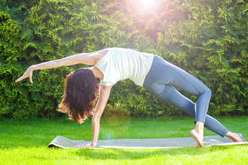 pretty adult woman doing yoga on a green grass