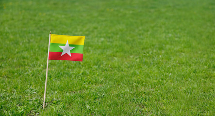 Myanmar flag. Photo of Myanmar flag on a green grass lawn background. Close up of national flag waving outdoors.