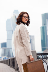 businesswoman with wooden case standing on background of business district
