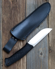 steel hunting knife near the leather sheath