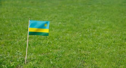 Rwanda flag. Photo of Rwandan flag on a green grass lawn background. Close up of national flag waving outdoors.