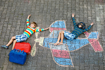 Two little children, kids boys having fun with with airplane picture drawing with colorful chalks on asphalt. Friends painting with chalk and going on vacations dreaming of pilot profession.